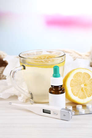 handkerchiefs: Hot tea for colds, pills and handkerchiefs on table on bright background Stock Photo