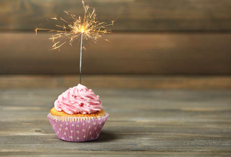 Cupcake avec sparkler sur la table sur fond de bois
