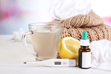 cold beverages: Hot tea for colds, pills and handkerchiefs on table on bright background Stock Photo