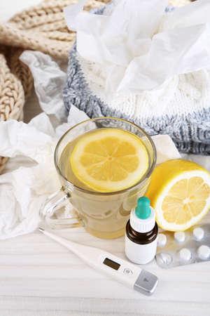handkerchiefs: Hot tea for colds, pills and handkerchiefs on table close-up