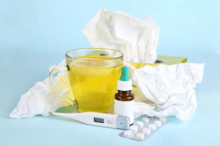 handkerchiefs: Hot tea for colds, medicine and handkerchiefs on blue background Stock Photo