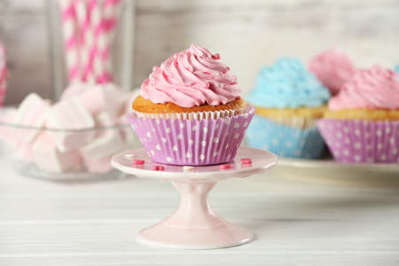 Delicious cupcakes on table on light background photo