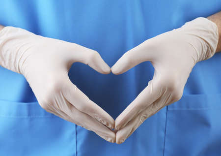 Doctor showing shape of heart by his hands in sterile gloves, closeup view Standard-Bild