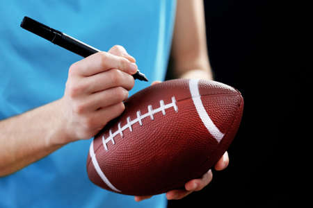 autograph: American football star signing autograph on ball on black background Stock Photo