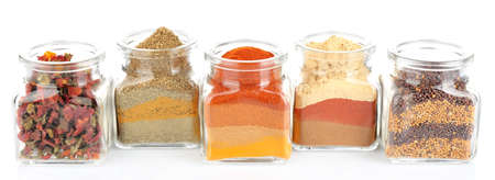 kinds: Different kinds of spices in glass bottles isolated on white