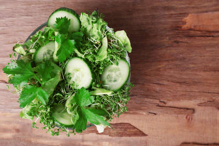 cress: Cress salad with sliced cucumber and parsley in glass bowl on rustic wooden table background
