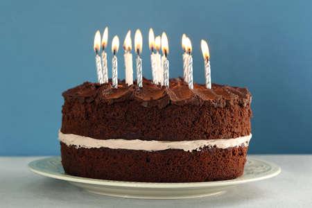 urodziny: Pyszne ciasto czekoladowe z świec na stole na niebieskim tle