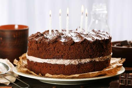 pasteles de cumpleaños: Delicioso pastel de chocolate en la mesa de luz de fondo