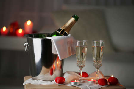 luxury hotel room: Champagne glasses and rose petals for celebrating Valentines Day, on dark background Stock Photo