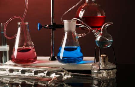 clavados: Fija la cristalería de laboratorio en apoyo sobre fondo de colores oscuros