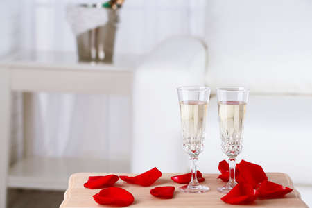 Champagne glasses and rose petals for celebrating Valentines Day photo