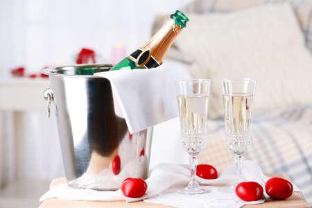 botella champagne: Botella de Champagne en cubo, las gafas y p�talos de rosa para celebrar el d�a de San Valent�n Foto de archivo