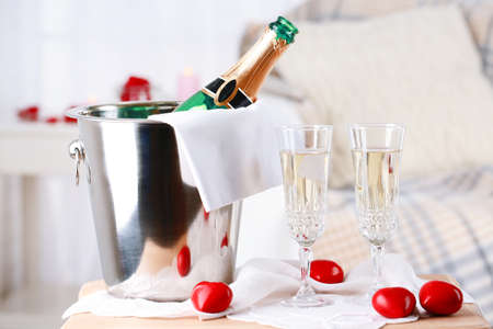 Champagne bottle in bucket,  glasses and rose petals for celebrating Valentines Day photo