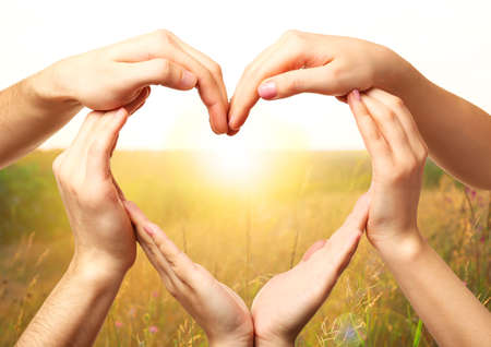 female hand: Heart shaped by hands on nature background