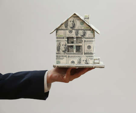 Model of house made of money in male hand on gray background photo