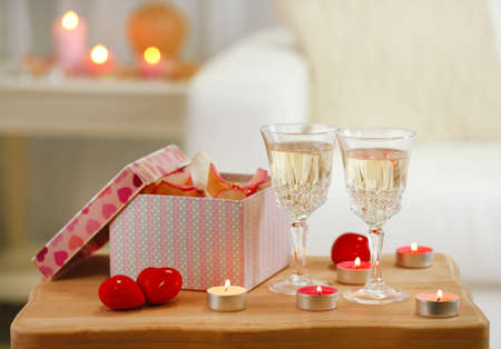 Champagne glasses, gift box and rose petals for celebrating Valentines Day photo