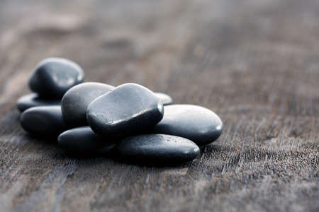 Stack of black sea pebbles on rustic wooden background photo