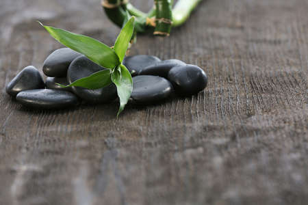 Stack of black sea paddles with green leaves and bamboo trunk on rustic wooden background photo