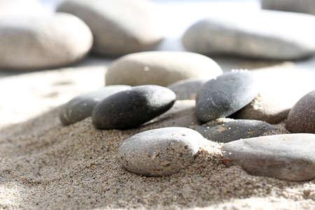 Gray sea pebbles on sand background Stock Photo