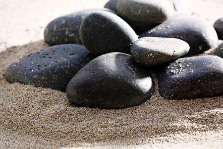 Pile of sea pebbles on shiny sand background photo