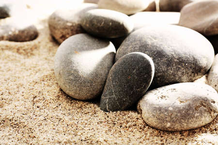 Gray sea pebbles on sand background photo