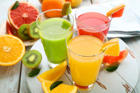 jugos: Los jugos frescos con frutas en la mesa de madera Foto de archivo