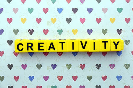 motto: Creativity motto by alphabet letters on surface with hearts on background
