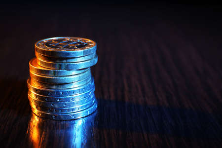 quid: Heap of coins on wooden table background Stock Photo