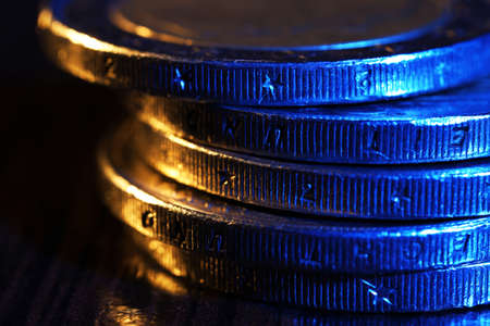 finance background: Heap of coins on wooden table, macro view