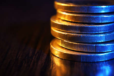 quid: Heap of coins on wooden table, macro view
