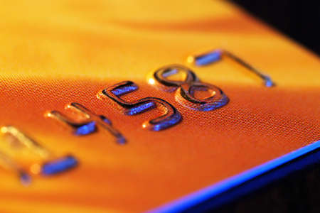 Numbers on plastic card on wooden table, macro view photo