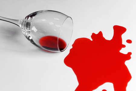 Red wine spilled from glass on white background Stockfoto