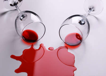 Red wine spilled from glass on white background photo