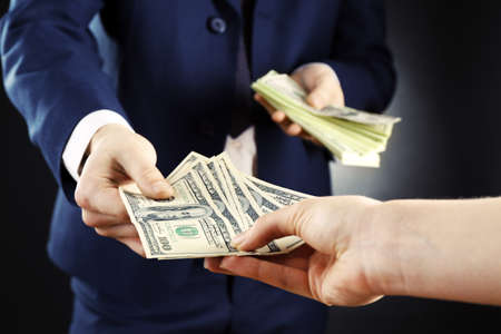 giving money: Businessman giving money on dark background