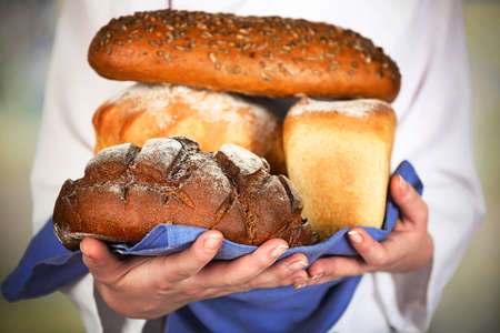 armful: Armful of freshly bread in female hands on light blurred background