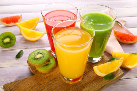 orange juice glass: Fresh juices with fruits on wooden table