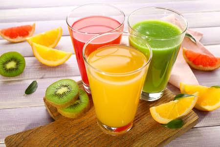 vaso de jugo: Los jugos frescos con frutas en la mesa de madera Foto de archivo