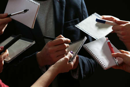 autograph: Elegant man signing autograph in notebook on dark background