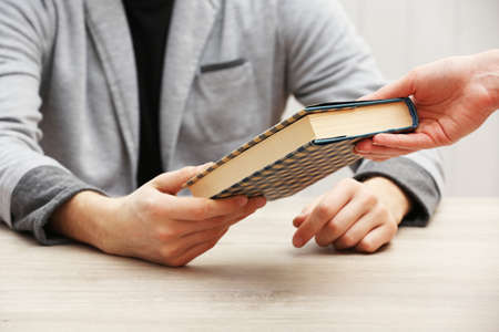 Author signing autograph in own book at wooden table on white planks background Archivio Fotografico