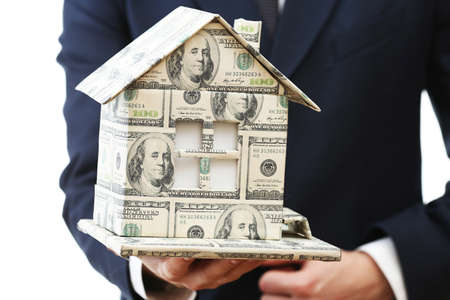 Model of house made of money in male hand isolated on white background photo
