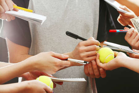 autograph: Sportsman signing autograph on tennis ball on dark background