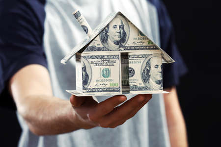 Model of house made of money in male hands on dark background photo