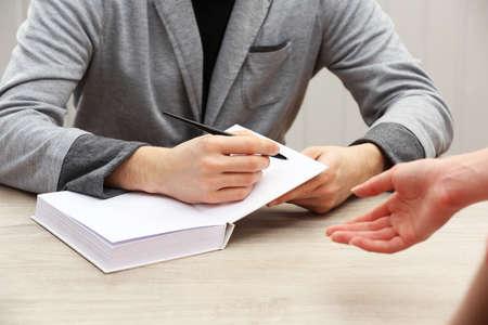 firmando: Autor firmando aut�grafos en el propio libro en la mesa de madera sobre fondo blanco tablones Foto de archivo