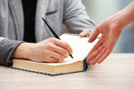 Author signing autograph in own book at wooden table on light blurred background Stock Photo