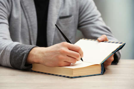 author: Author signing autograph in own book at wooden table on light blurred background Stock Photo