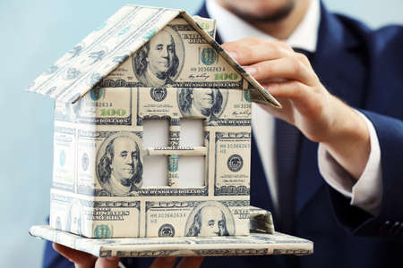 Model of house made of money in male hands on white background photo