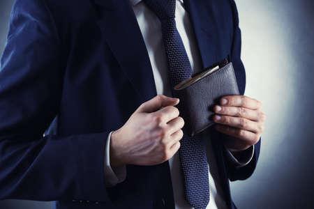 Lederen portemonnee met geld in mannelijke handen op een donkere achtergrond