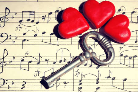music book: Retro key with hearts on music book background Stock Photo