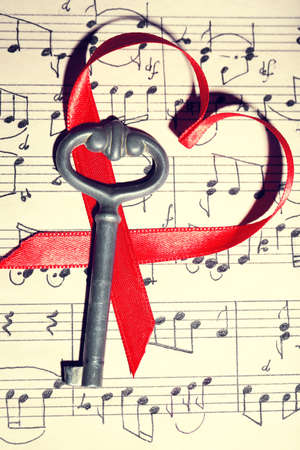 music book: Retro key with heart on music book background
