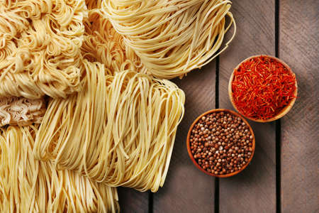 Different dry instant noodles with spices on wooden background photo
